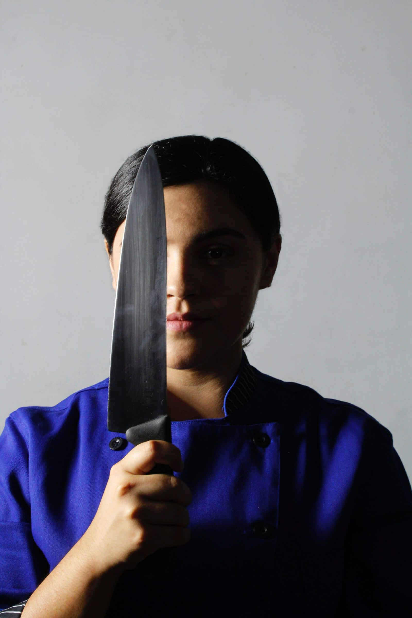 a chef hiding half of her face using a knife