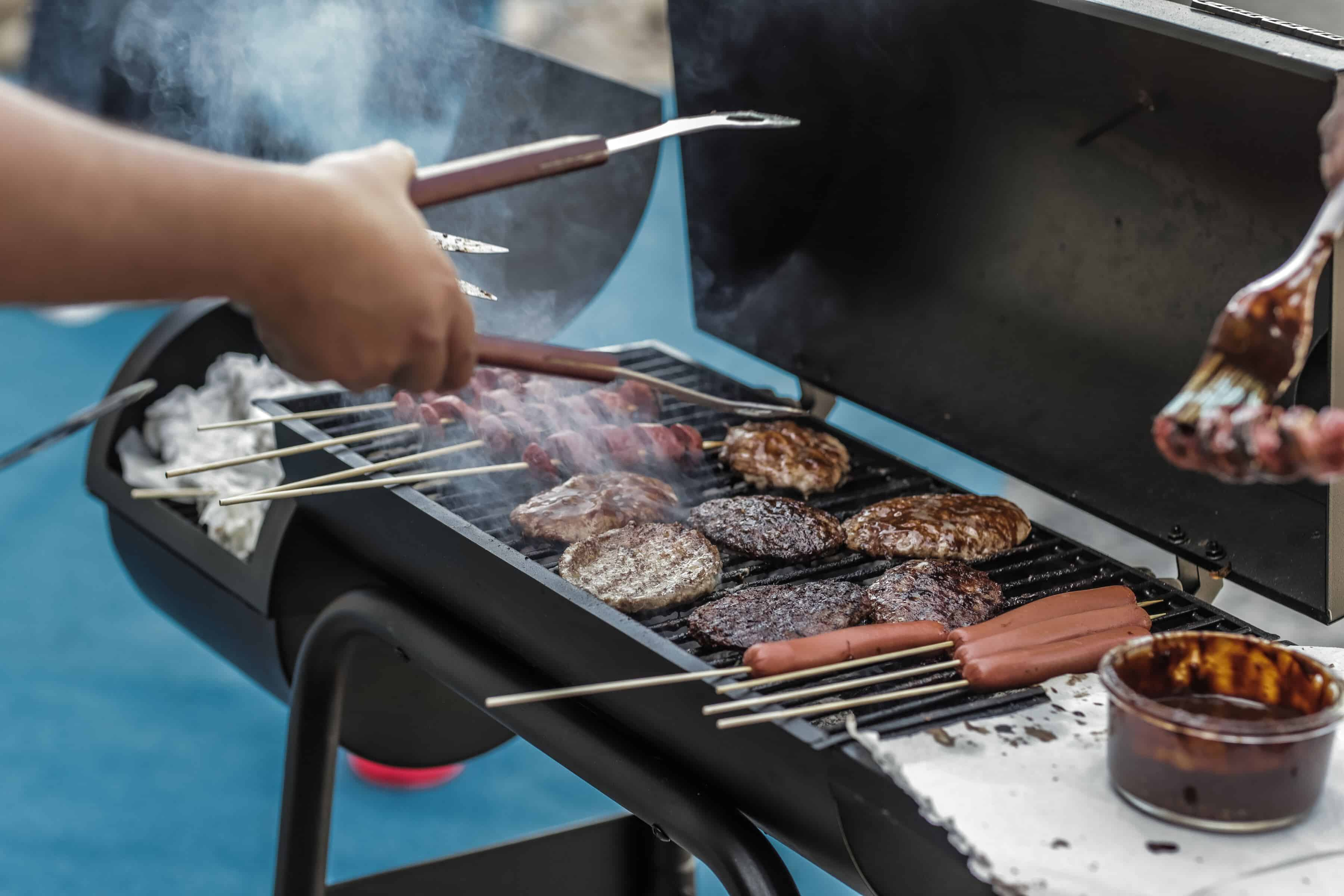 a person is grilling sausages and meat with bbq smoker