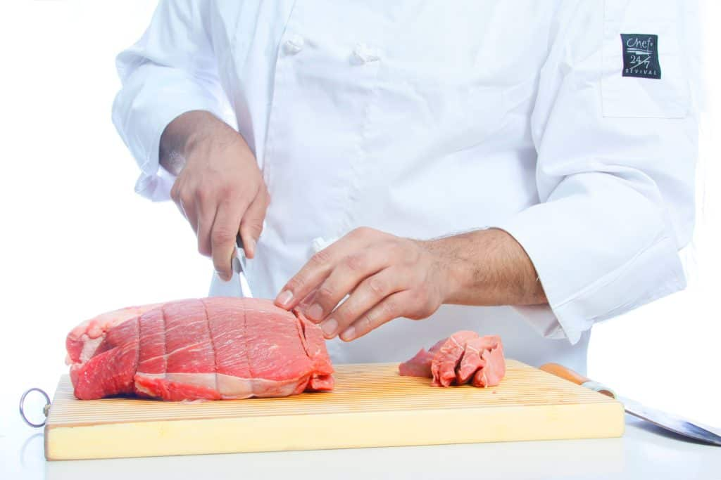 a chef is cutting the meat with a knife
