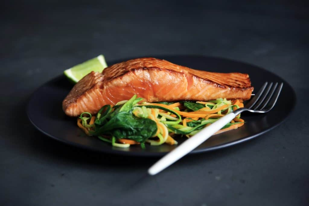 grilled salmon, cooked vegetables, and fork on plate