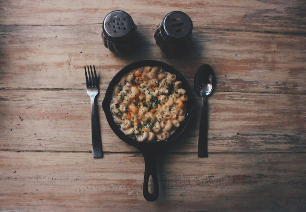 a pan of mac and cheese beside fork and spoon on brown wooden table