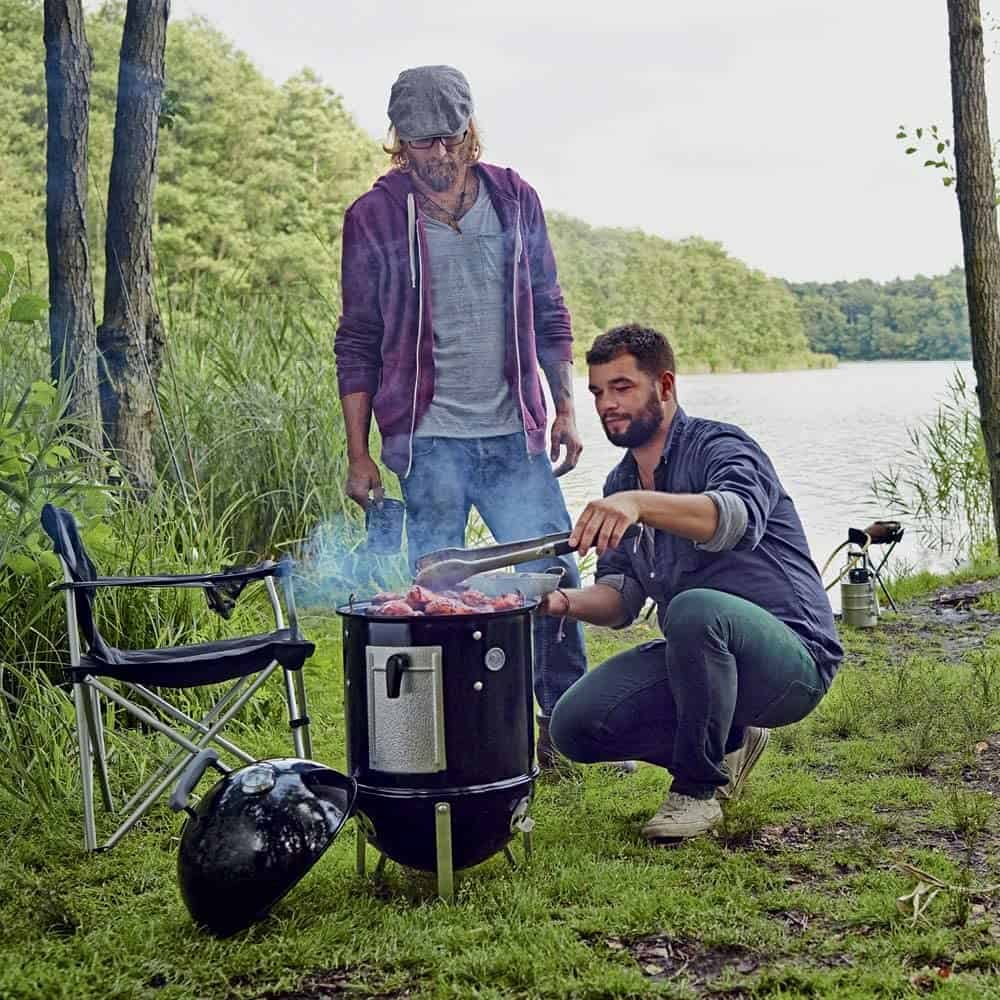 Easy to use charcoal grill for beginners- Weber 14-inch Smokey Mountain Cooker being used outdoors